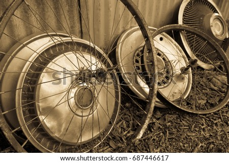 sepia colored image with circular shapes of antique bicycle wheels and old hubcaps from the