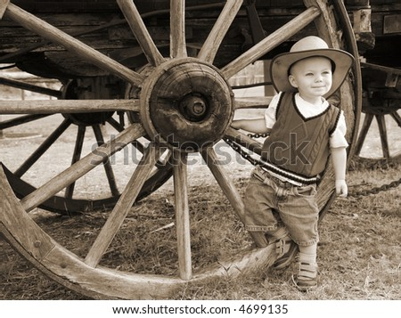 Sepia Farmboy:  A baby cowboy hangs out at the wheel of an old farm wagon in a cowboy hat and denim shorts.