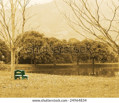 sepia image of a landscape with green bench
