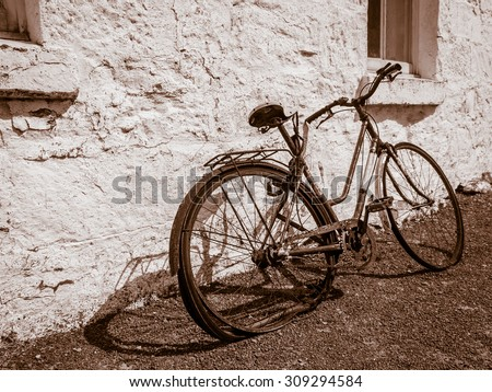 Sepia Image of Broken Old Bicycle Leaning Against Whitewashed Stone Wall - stock photo