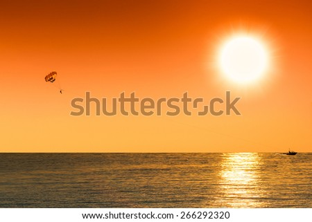 sepia silhouette of parasailing man on the sunset  - stock photo