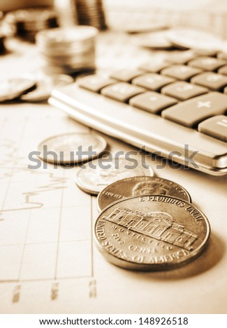 Sepia tint of calculator and coins on business chart - stock photo