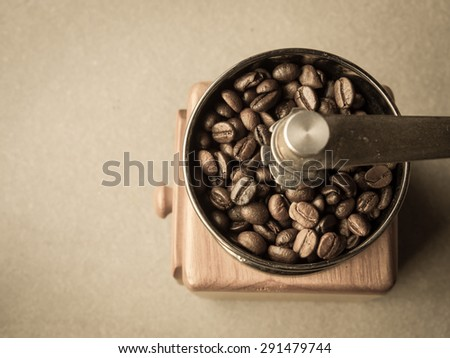 Sepia tone and retro style photo of  roasted coffee beans in a coffee grinder on cement background. - stock photo