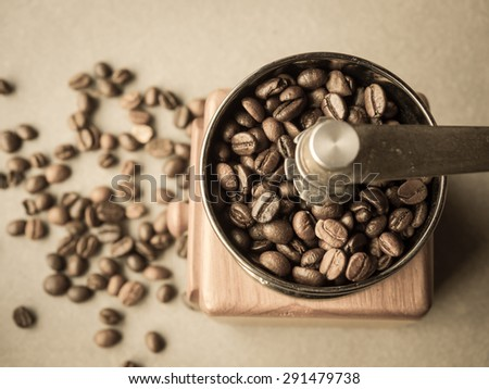 Sepia tone and retro style photo of  roasted coffee beans in a coffee grinder with blur  coffee beans background. - stock photo