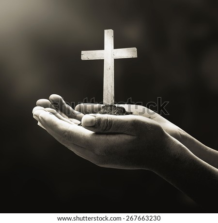 Sepia tone. Human hands holding the wooden white cross. - stock photo