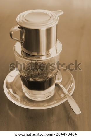 """sepia tone of Vietnamese coffee , the traditional Vietnamese coffee brewing coffee by """"Phin"""" (traditional coffee maker . Normally served with condensed milk at the bottom of clear glass  - stock photo"""