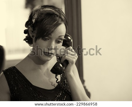 Sepia tone retro photo of a woman in a flapper dress and head dress talking on an old telephone. - stock photo