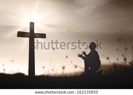 Sepia tone. Silhouette human kneeling and praying over the cross on beautiful sunset with amazing light background. - stock photo