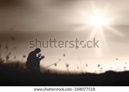 Sepia tone. The lonely man. People kneeling and praying over blurred the white cross on sunset background. - stock photo