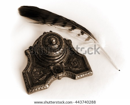 Sepia toned Antique Bronze inkpot with feather on white background with shadows - stock photo
