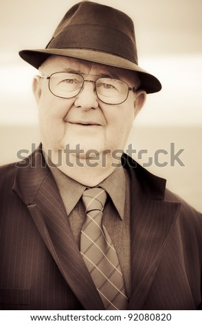 Sepia Toned Close-up Face Portrait Of A Retro Senior Male In Business Attire Displaying An Expression Of Fascination Interest And Enthrallment - stock photo
