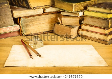 Sepia toned image of vintage fountain pens with blank paper in front of old books on a table - stock photo