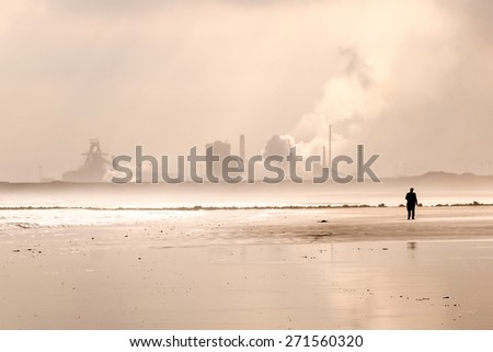 sepia toned landscape of a silhouette and power station on a beach - stock photo