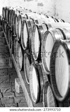 Sepia toned photo of winery cellar with wooden barrels - stock photo