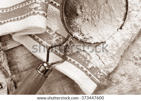 Sepia toned rustic still-life of baking flour with vintage sieve and kitchen towel on distressed wood.