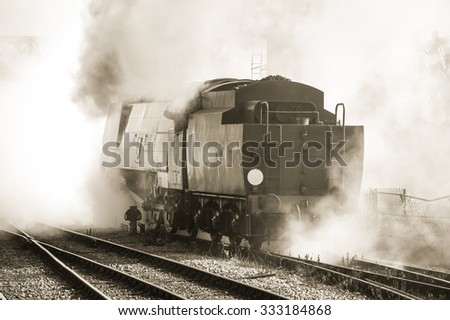 sepia toned vintage locomotive in a cloud of steam - stock photo
