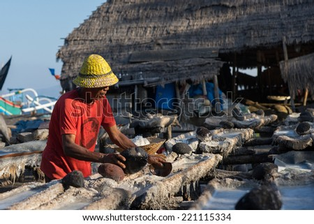 SEPTEMBER 18, 2014 - BALI, INDONESIA: A worker scoops the salt grains from the evaporation platforms after the drying process. Sea salt manufacturing is a traditional cottage industry of Bali.  - stock photo