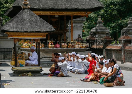 SEPTEMBER 18, 2014 - BALI, INDONESIA: Hindu devotees pray at the Tirta Empul Temple led by a high priest.  Hinduism is the religion of the majority of the Balinese people. - stock photo