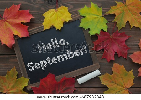 September Concept. Hello September Words On Chalkboard. Dark Brown Wooden  Background. Top View