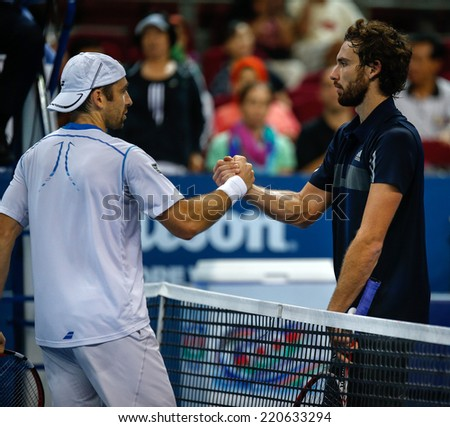 SEPTEMBER 26, 2014 - KUALA LUMPUR, MALAYSIA: Benjamin Becker (white) shakes Ernests Gulbis' hands after their match at the Malaysian Open Tennis 2014. This event is an ATP sanctioned tournament. - stock photo