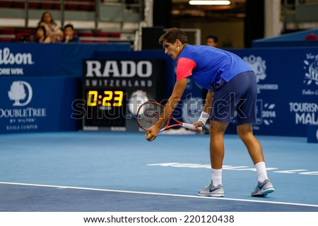 SEPTEMBER 23, 2014 - KUALA LUMPUR, MALAYSIA: Pierre-Hugues Herbert of France prepares to make a serve in his first round match at the Malaysian Open Tennis 2014. This is an ATP sanctioned tournament. - stock photo