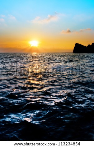 September Sunset over water viewed from the jetty that juts out at the mouth of Anchor Bay, Malta - stock photo