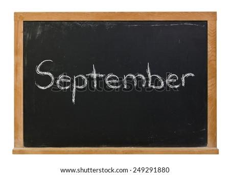 September written in white chalk on a black wood framed chalkboard isolated on white - stock photo