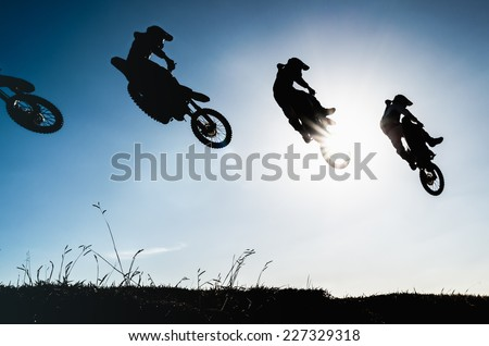 Sequence of a motocross jump in silhouette with blue sky and sun - stock photo