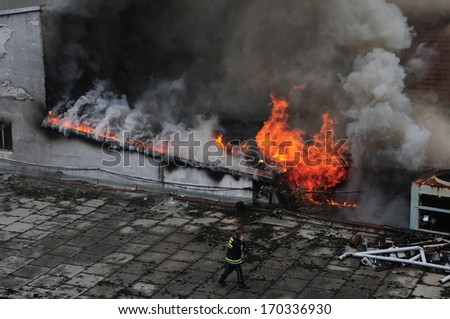 "SERBIA, BELGRADE - MAY 25, 2012: Firefighters in action trying to control fire in ""Kozara"", one of the oldest cinema theatres in Belgrade"