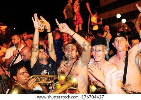 SERBIA, GUCA - AUGUST 8, 2012: People dancing to the rhythm of brass band at Guca Trumpet Festival