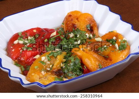 Serbian yellow and red grilled peppers salad in a white plate