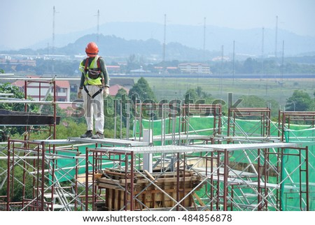 SEREMBAN, MALAYSIA -AUGUST 05, 2016: Construction workers wearing safety harness and adequate safety gear while working at high level at the construction site in Seremban, Malaysia.