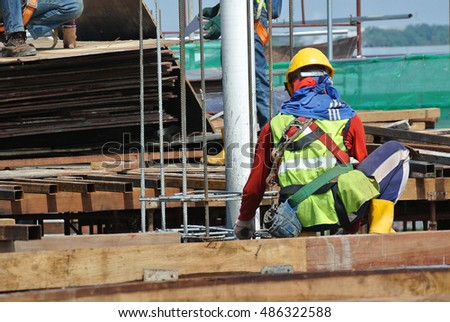 SEREMBAN, MALAYSIA -JULY 01, 2016: Construction workers working at the construction site at Seremban, Malaysia during daytime. They are wearing proper safety gear to ensure they are safe working.