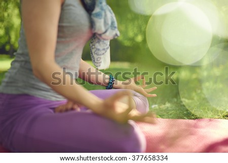 Serene and peaceful woman practicing mindful awareness by meditating in nature at sunset with background bokeh. - stock photo