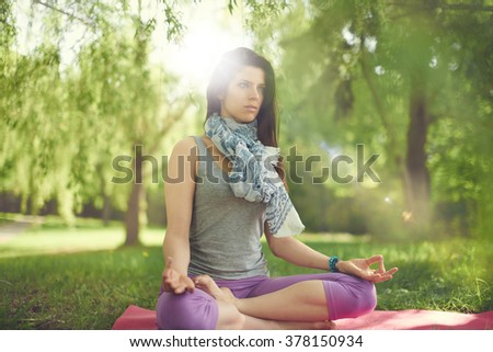 Serene and peaceful woman practicing mindful  awareness by meditating in nature with sun flare. - stock photo