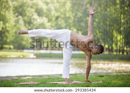 Serene attractive Indian young man in white linen clothes working out on lake in park, standing in ardha chandrasana (Half Moon Pose), full length - stock photo