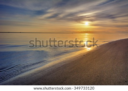 Serene beach and sky, with the sun peeking through playful clouds  - stock photo