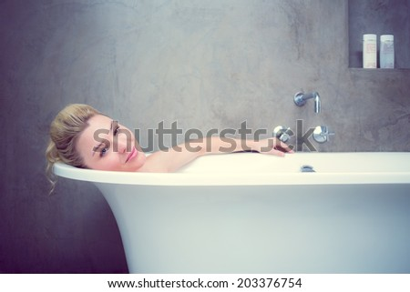 Serene blonde lying in the bath smiling at camera at home in the bathroom - stock photo