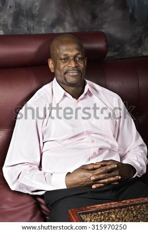 Serene contented guy sitting on leather sofa palms folded - stock photo