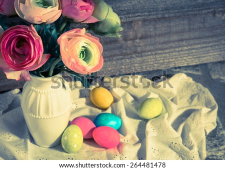 Serene Easter Still Life of Flowers in Vase with Dyed Eggs on Cloth with side lighting on Rustic Wood Wall Board Background with room or space for copy, text, your words.  Horizontal moody instagram