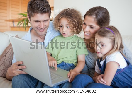 Serene family using a laptop in their living room