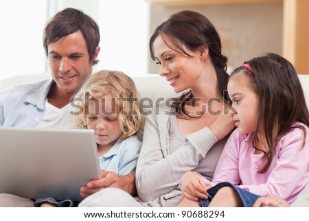 Serene family using a notebook in a living room - stock photo