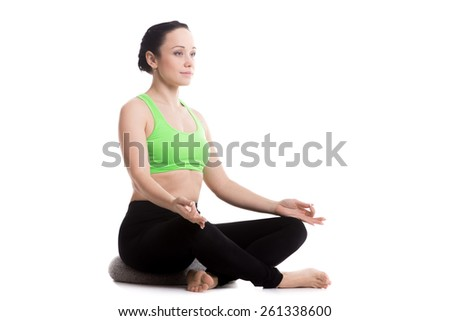 Serene girl practicing yoga, Sitting on pillow in Easy (Decent, Pleasant Pose), Sukhasana, asana for meditation, breathing, relieving stress, copy space - stock photo