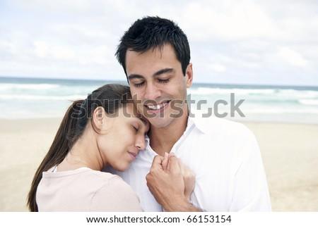 serene hispanic couple bonding on beach smiling - stock photo