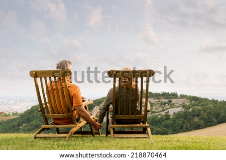 Serene mature couple holding hands together and looking at their future - stock photo