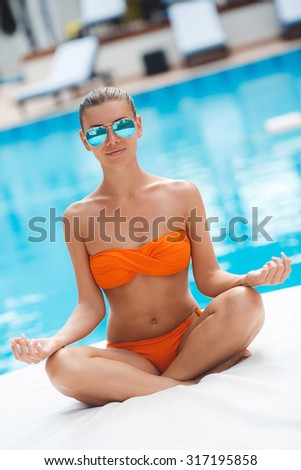 Serene meditating woman relaxing at luxury travel holiday vacation resort. Happy blissful asian young woman in bikini in meditation enjoying summer sun and tanning at Spa resort. - stock photo