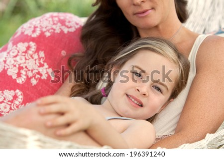 Serene mother and young daughter relaxing together on a hammock in a holiday home garden with green grass during a sunny summer day. Family activities and lifestyle outdoors, close up portrait. - stock photo
