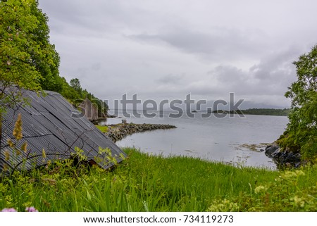 Serene Scandinavian landscape seascape on a rainy day with blue skies and puffy clouds.