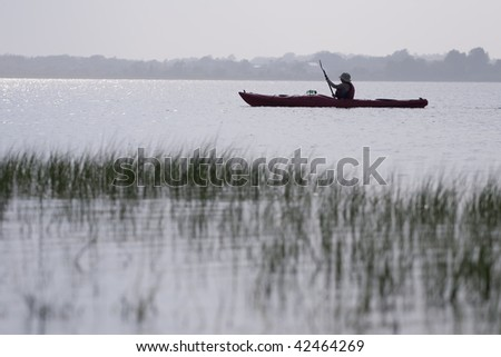 Serene scene of woman kayaking.