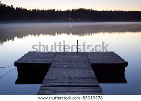 Serene scene with jetty photographed at twilight - stock photo